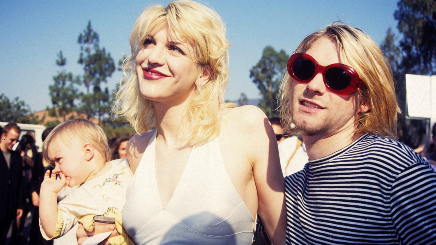 Kurt Cobain of Nirvana (right) with wife Courtney Love and daughter Frances Bean Cobain at the Universal Ampitheater in Universal City, California (Photo by Terry McGinnis/WireImage)